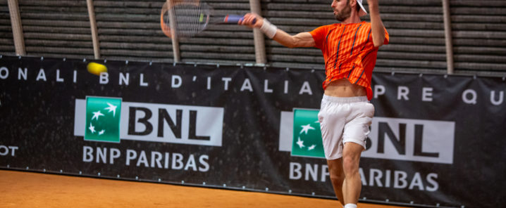 ragazzo con maglietta arancione che gioca a tennis