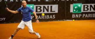 ragazzo con maglietta azzurra che gioca a tennis